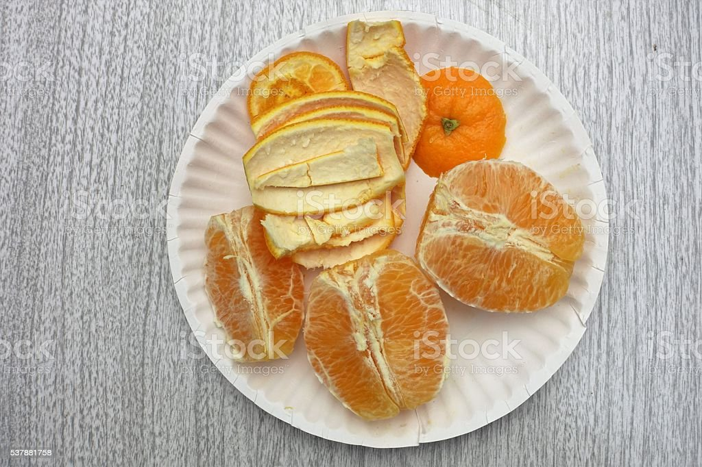 Navel orange peeled and pulled apart on plate stock photo