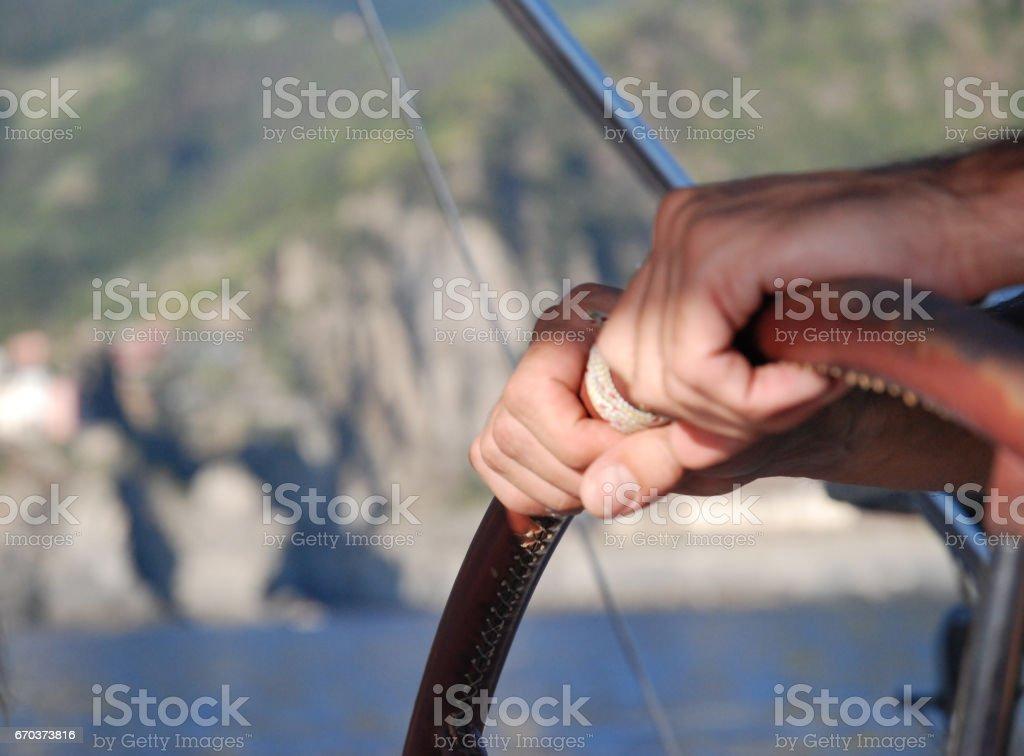 navigando in barca a vela, mani sul timone stock photo