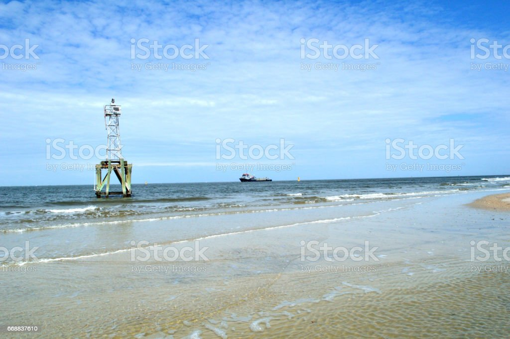 Navigation beacon with freight ship in background stock photo