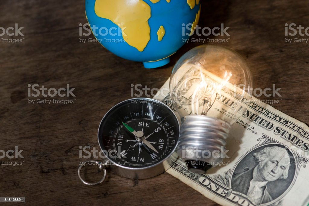 Navigation compass, lit light bulb, and a world globe on top of a US one dollar bill, with a wooden background stock photo