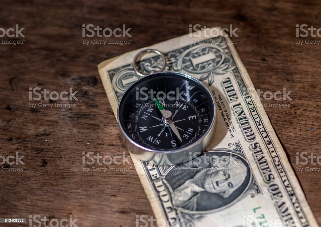 Navigation compass on top of a dollar bill, and a wooden background, money and direction concept stock photo