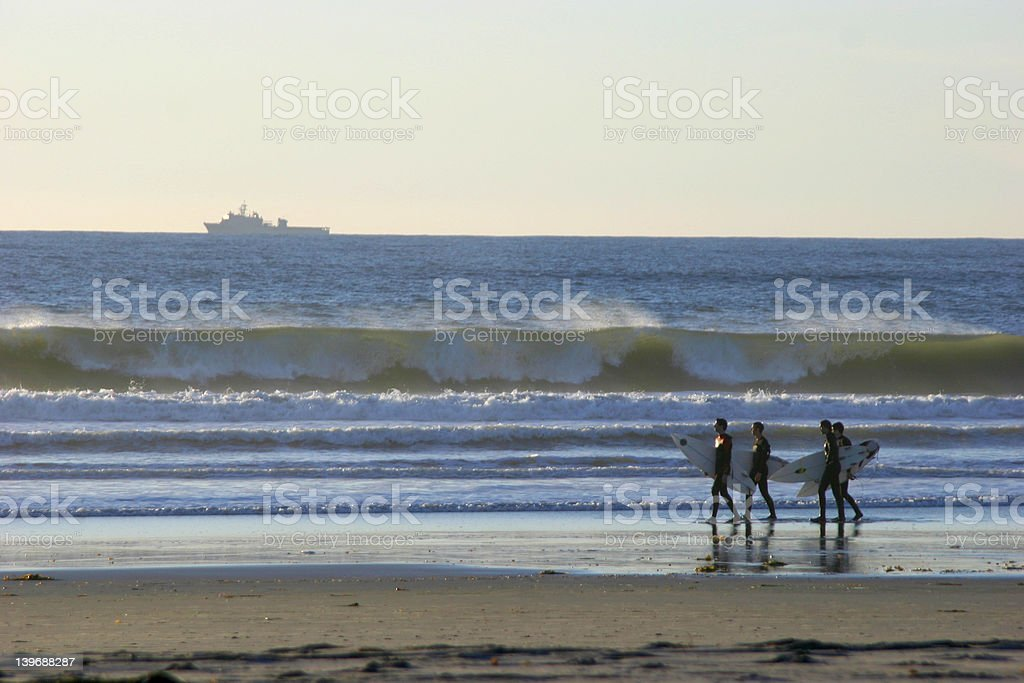 US Navy battleship and group of surfers stock photo