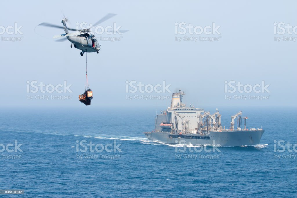 Navy helicopter delivering goods to ship stock photo
