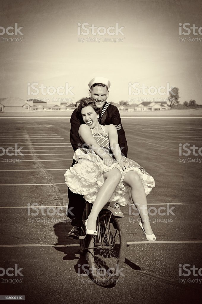 WWII Navy Man and His Pretty Woman Riding A Bike stock photo