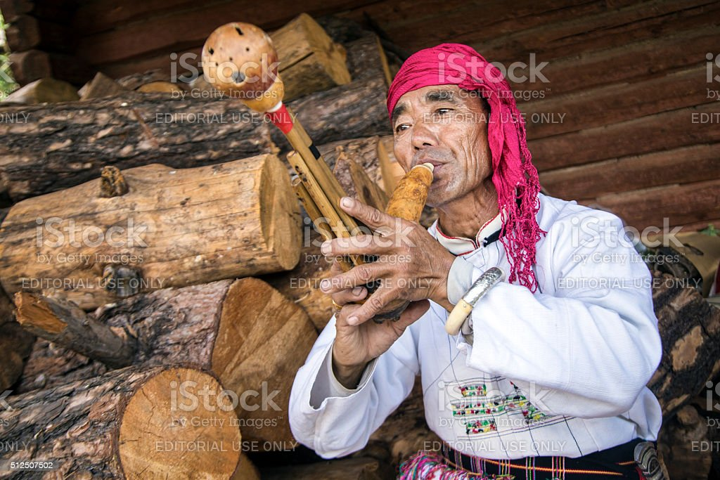 Naxi man playing a gourd mouth organ stock photo