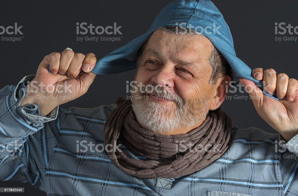 ndoor portrait of senior man in blue shirt and cap stock photo