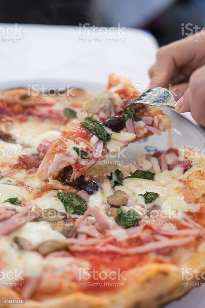 Neapolitan  pizza with a slice getting taken out stock photo