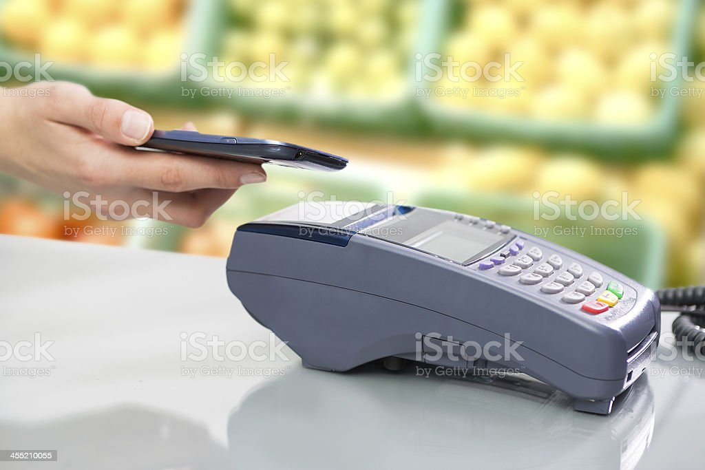 Near field communication device with phone held close stock photo