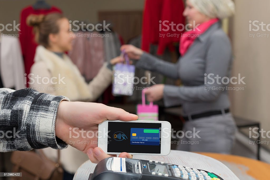 Near Field Communication - Man completing mobile Payment Woman shopping stock photo