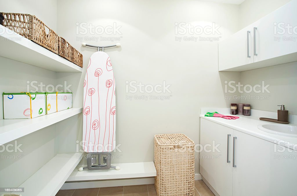 Neat and clean laundry room with hamper and ironing board  stock photo