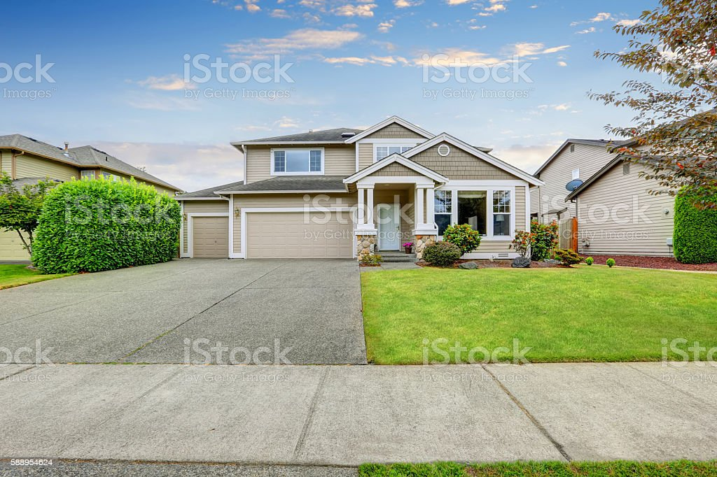 Neat beige home with two garage spaces. stock photo