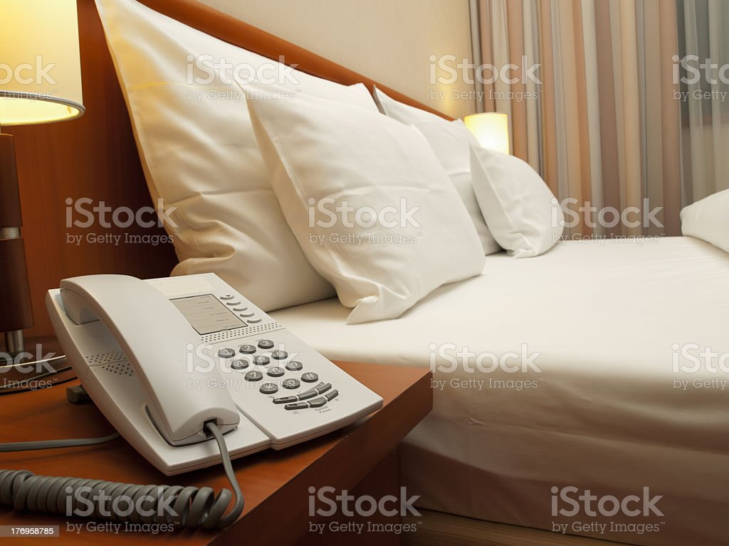 Neat hotel room featuring queen-size bed and bedside phone royalty-free stock photo