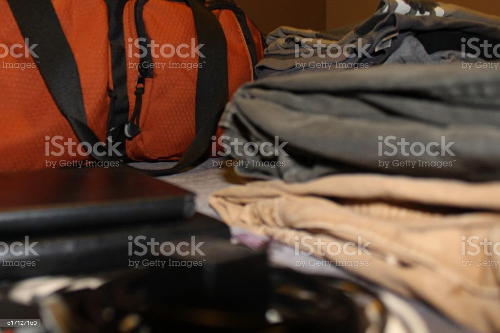 Neatly Folded Clothes in front of Orange Duffle Bag stock photo