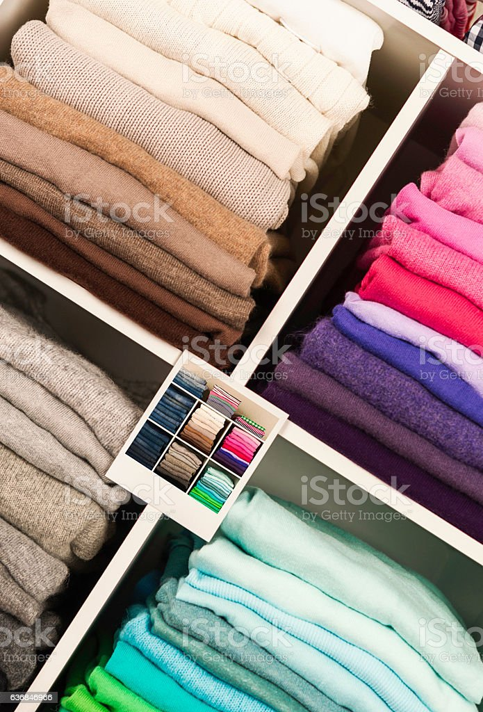 Neatly organized clothing in cubicles with photo guide for clothing stock photo