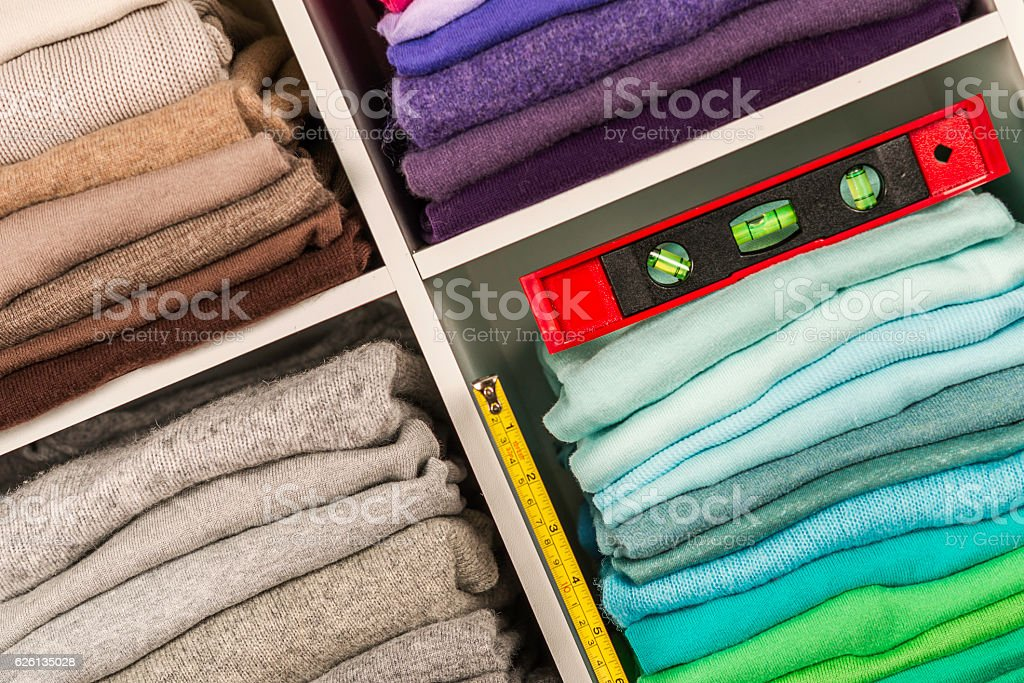Neatly organized clothing in cubicles with spirit level and ruler stock photo