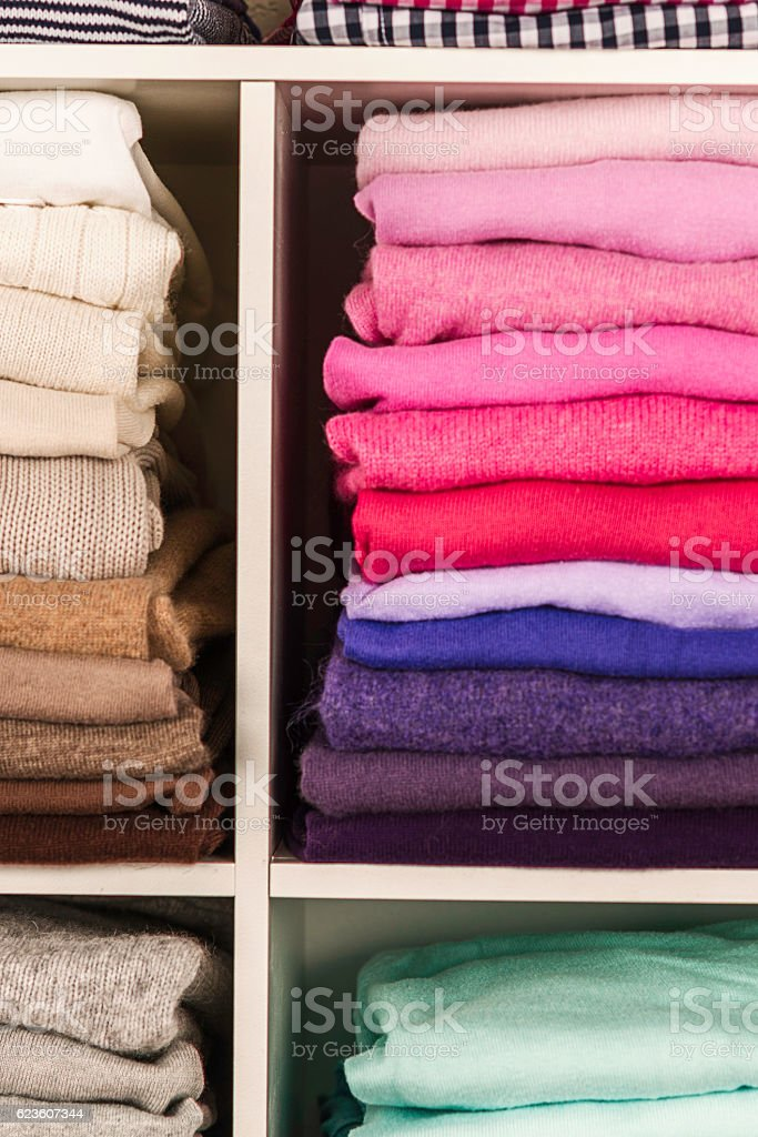 Neatly organized womens clothing in white cubicles stock photo