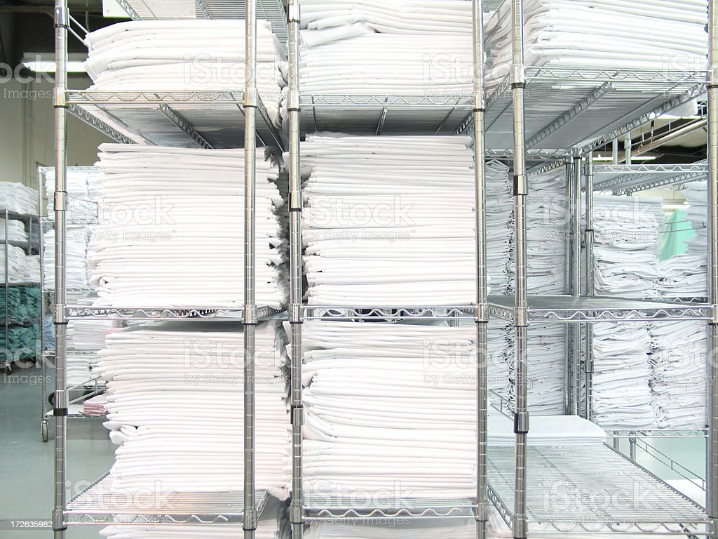 Neatly Stacked White Linen on Silver Chrome-plated Shelves royalty-free stock photo
