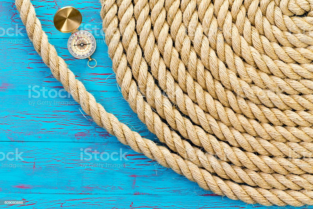 Neatly wound and coiled rope with compass stock photo