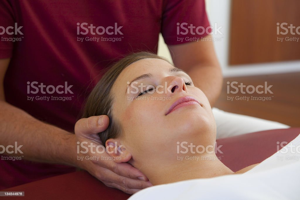 Neck- and head massage of a young woman stock photo