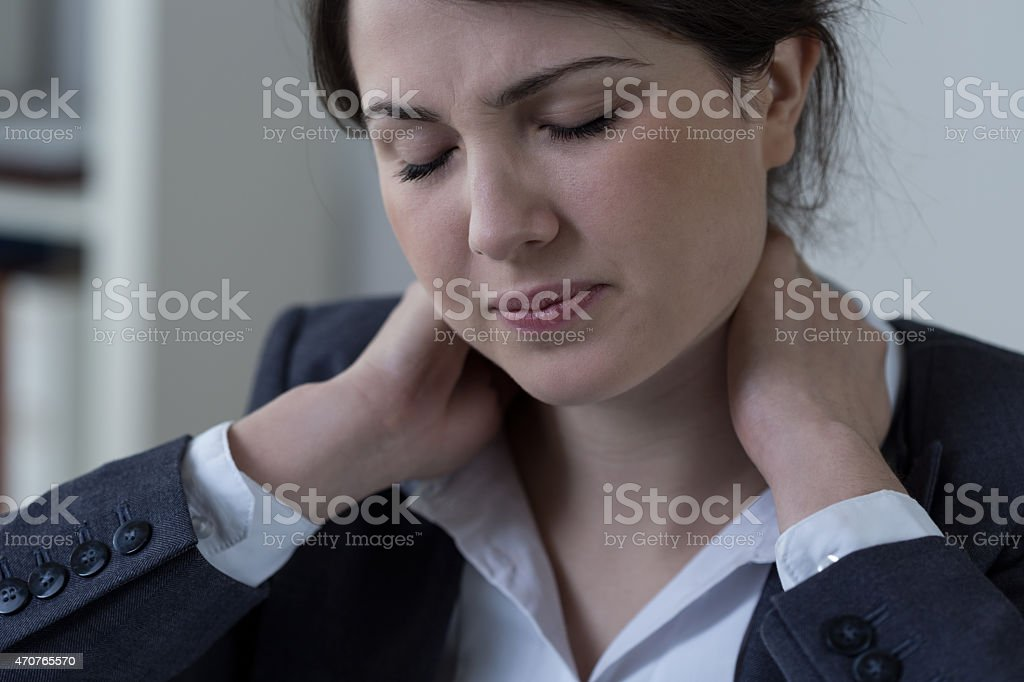 Neck pain, caused by incorrect sitting position at her desk  stock photo