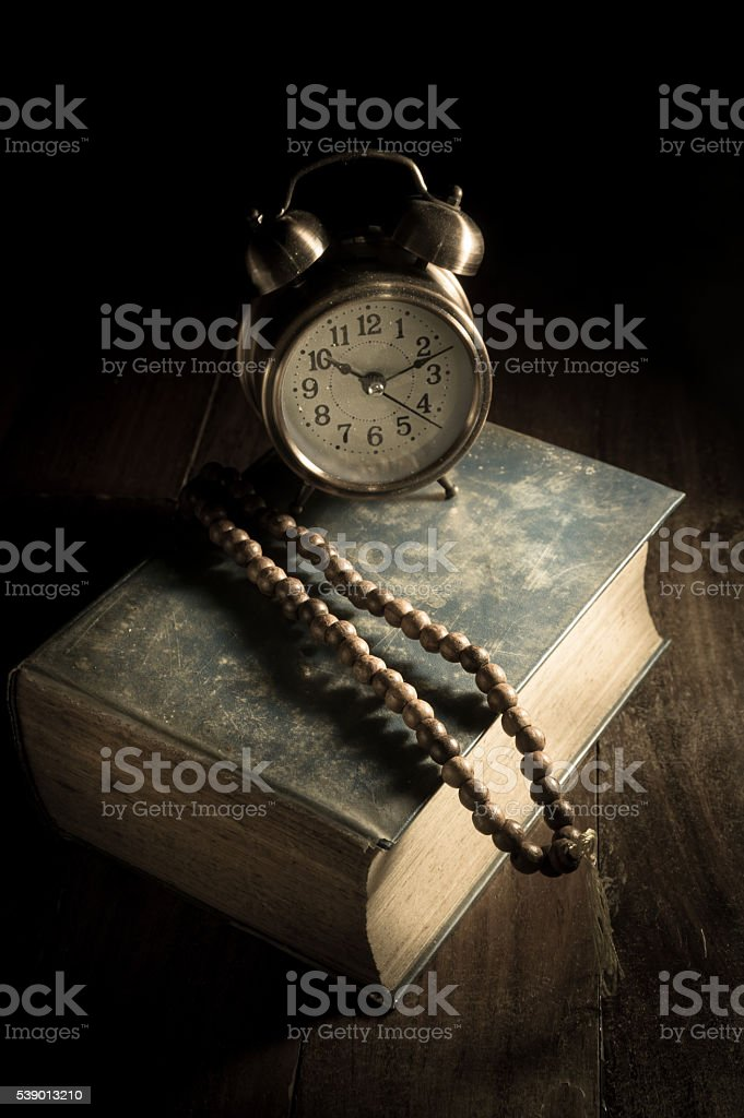Necklace with old book and alarm clock stock photo