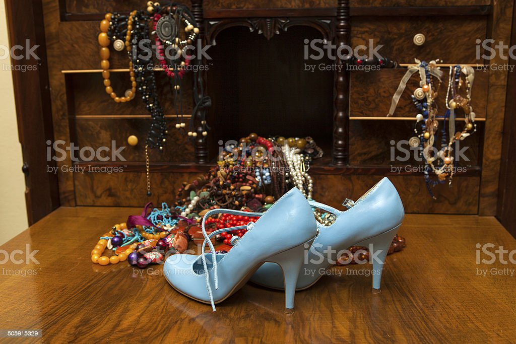 Necklaces and high heels on dresser stock photo