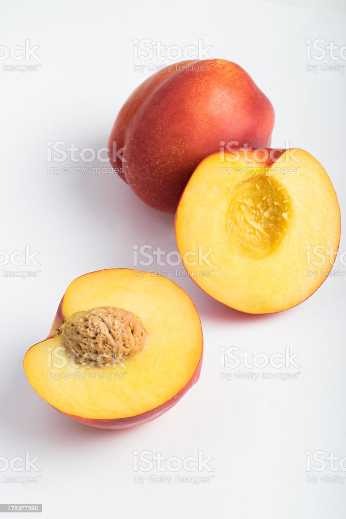 Nectarines cut in half over white background stock photo