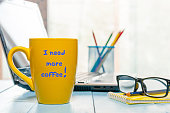 I need more coffee written on big yellow cup with