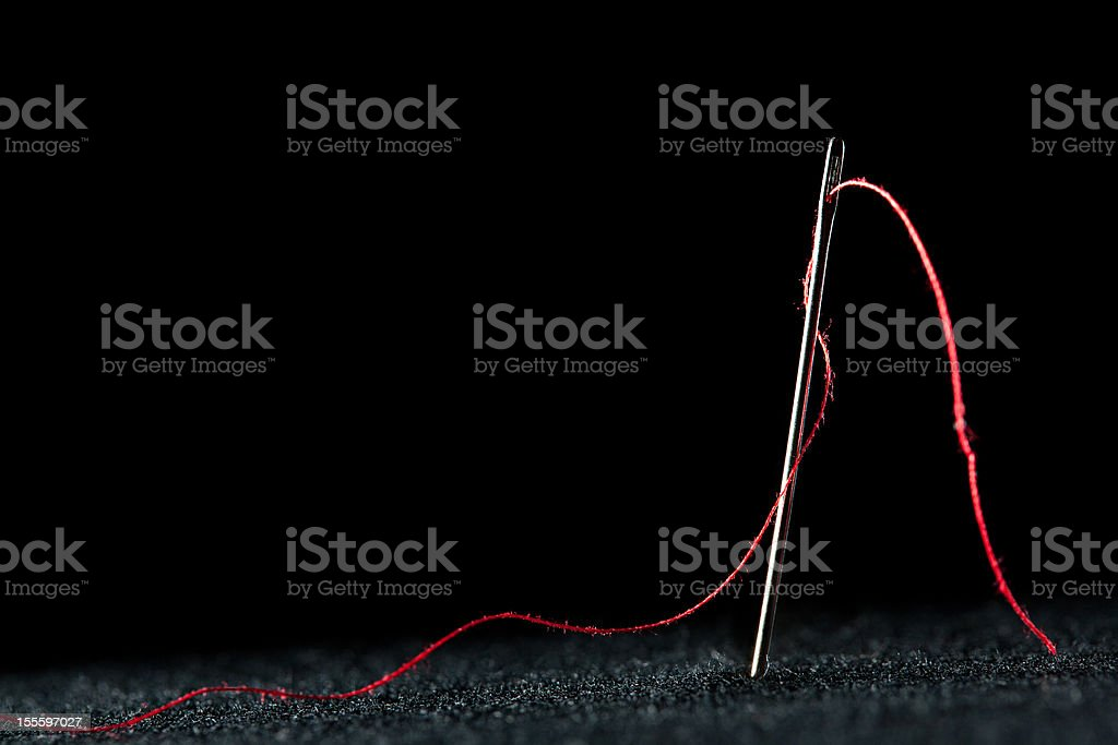 Needle and red thread stock photo