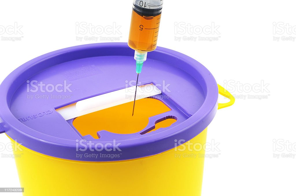 Needle and Syringe going into a Sharps Bins royalty-free stock photo