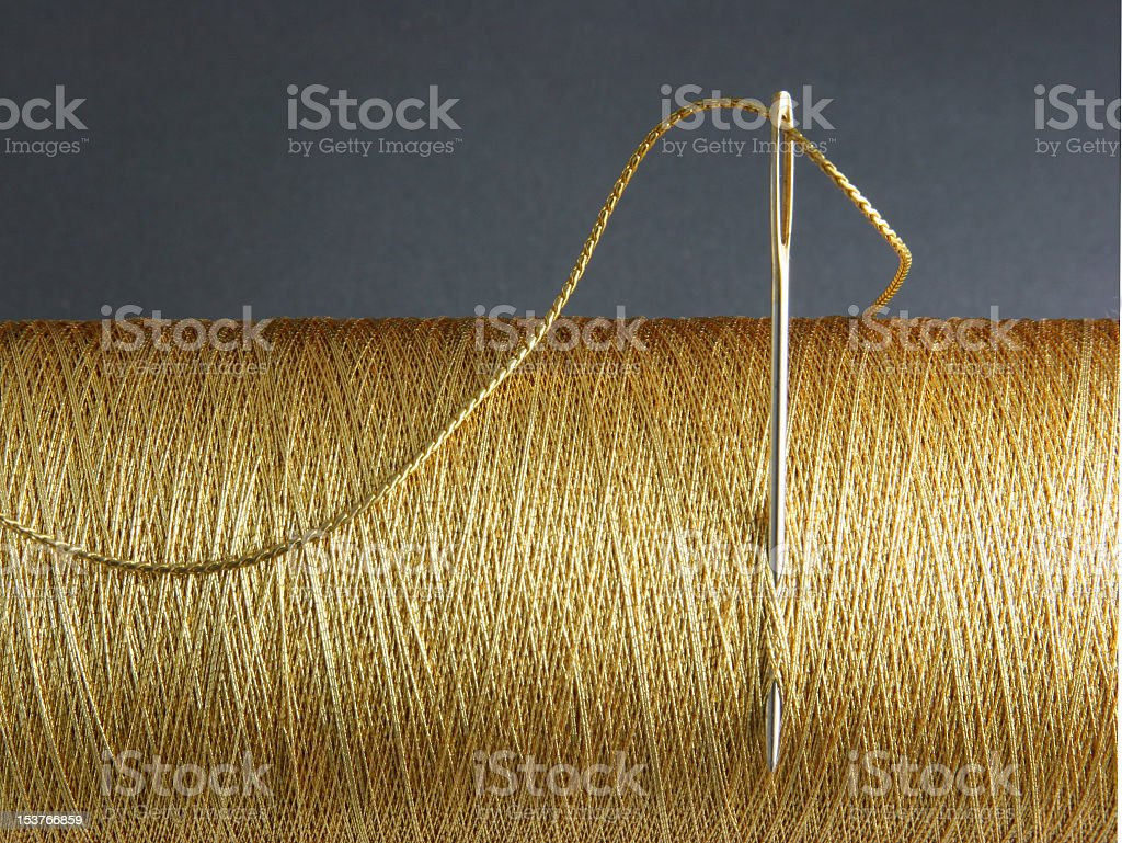 A needle stuck in a spool of thread stock photo