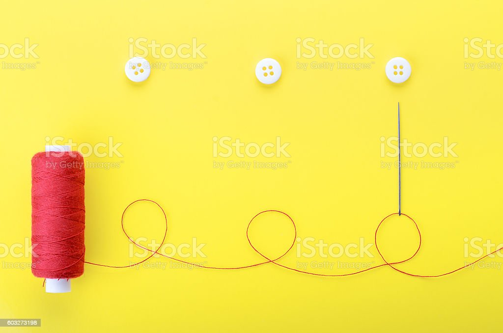needle with the red thread and clothing buttons stock photo