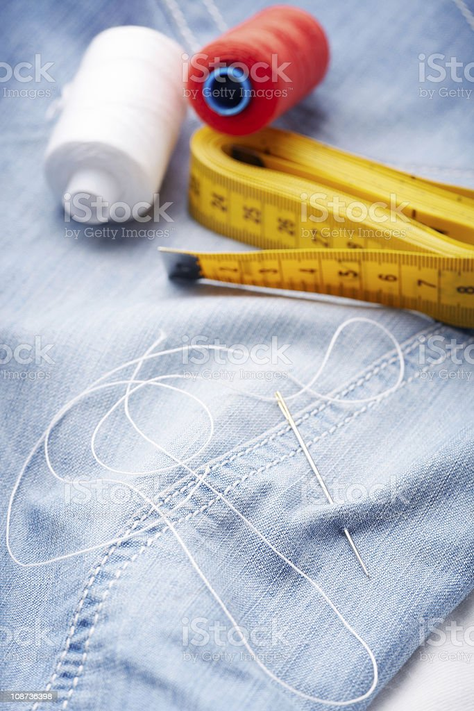 Needle with thread and ruler on jeans material royalty-free stock photo