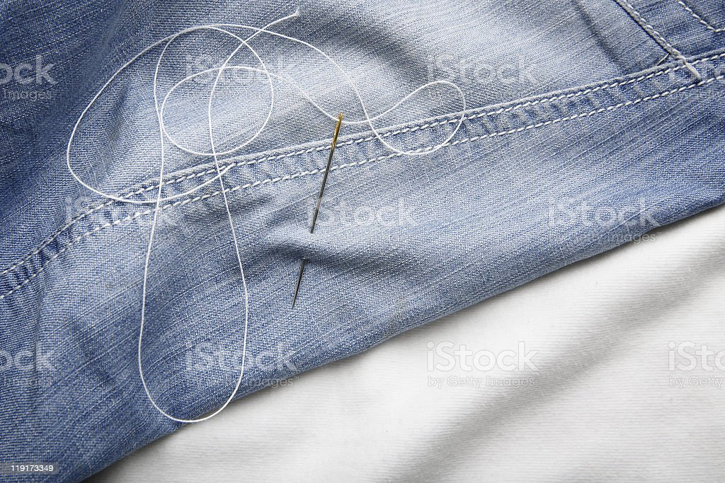 Needle with thread on jeans material royalty-free stock photo