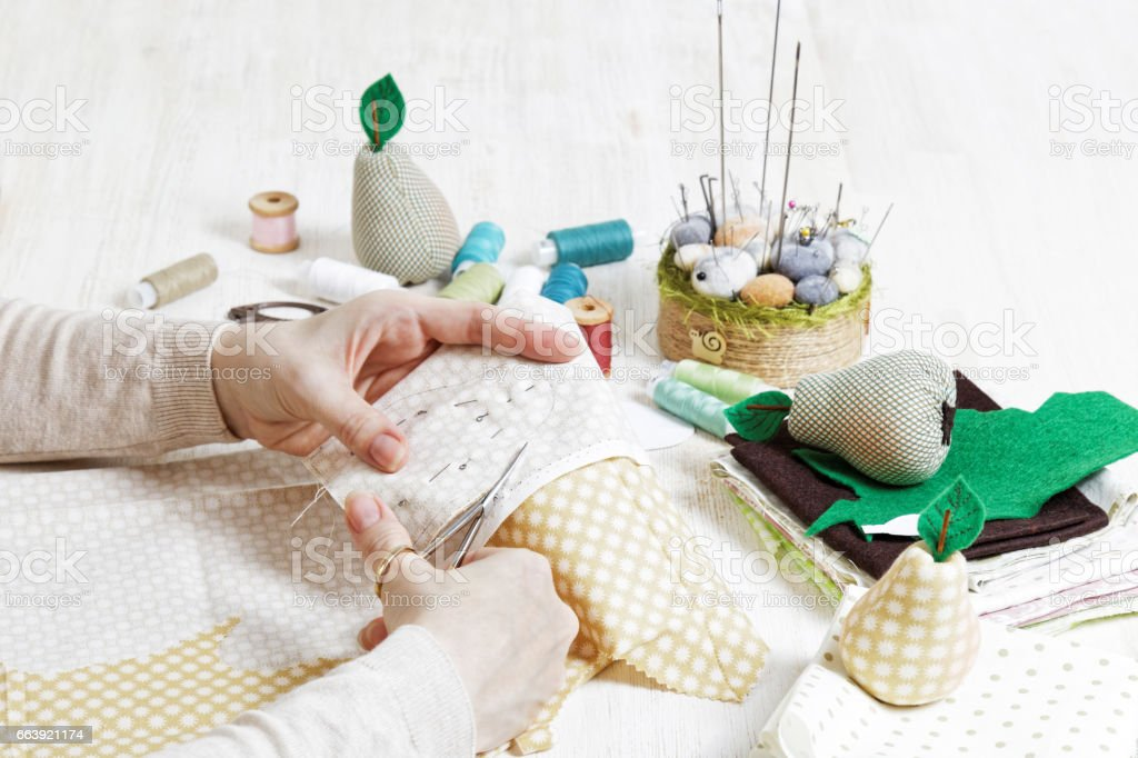 Needlewoman cuts out a pattern for the handmade toy with scissors. stock photo