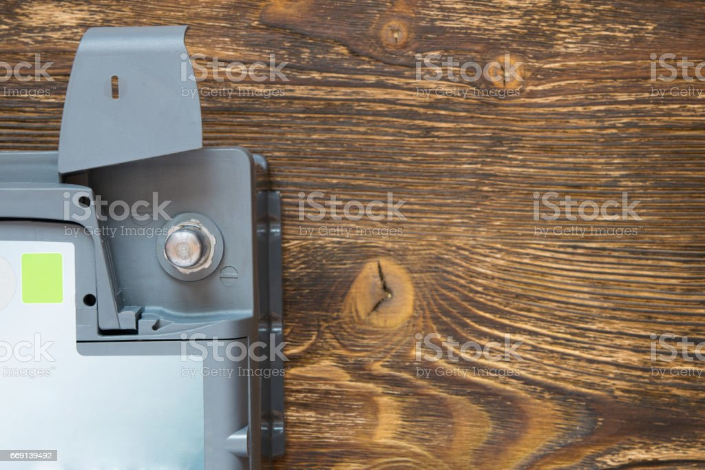 negative battery terminal in the corner of a wooden background stock photo