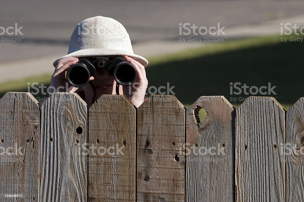 A neighbor dying over a fence wearing binoculars stock photo