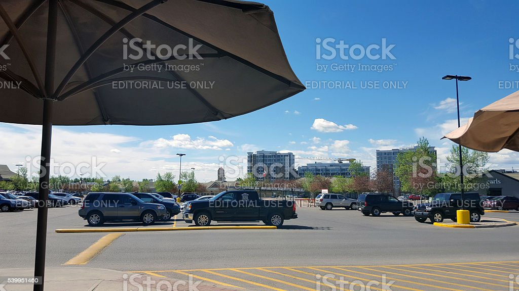 Neighborhood Shopping Center Parking Lot With Trees And Umbrellas stock photo