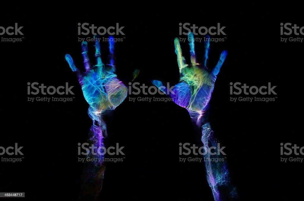 Neon paint on hands under fluorescent lighting stock photo