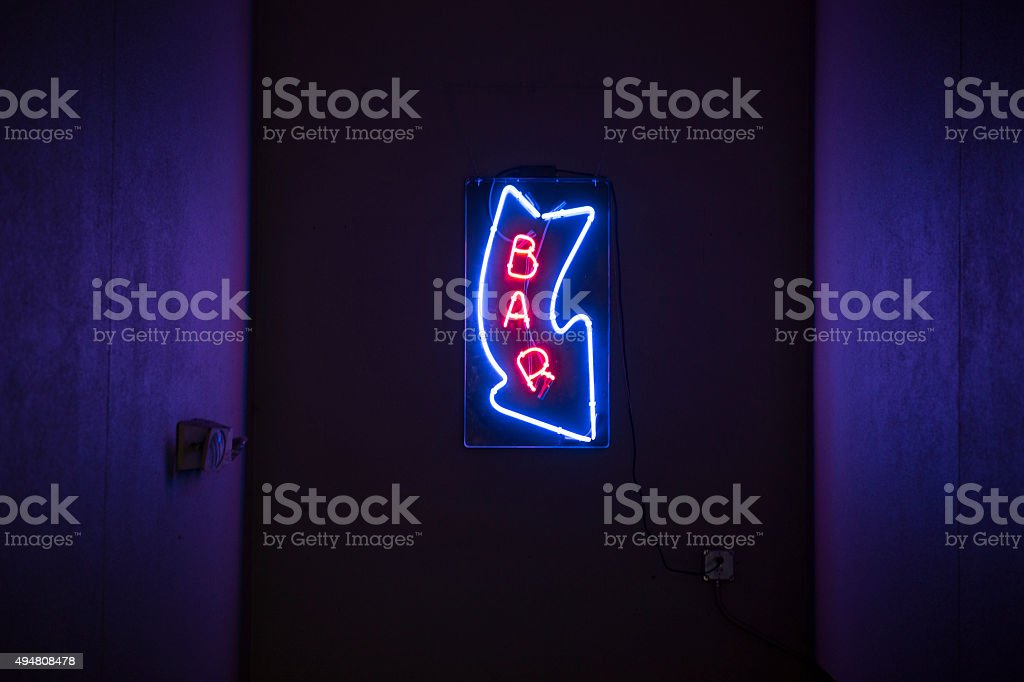 Neon sign pointing down to a bar stock photo