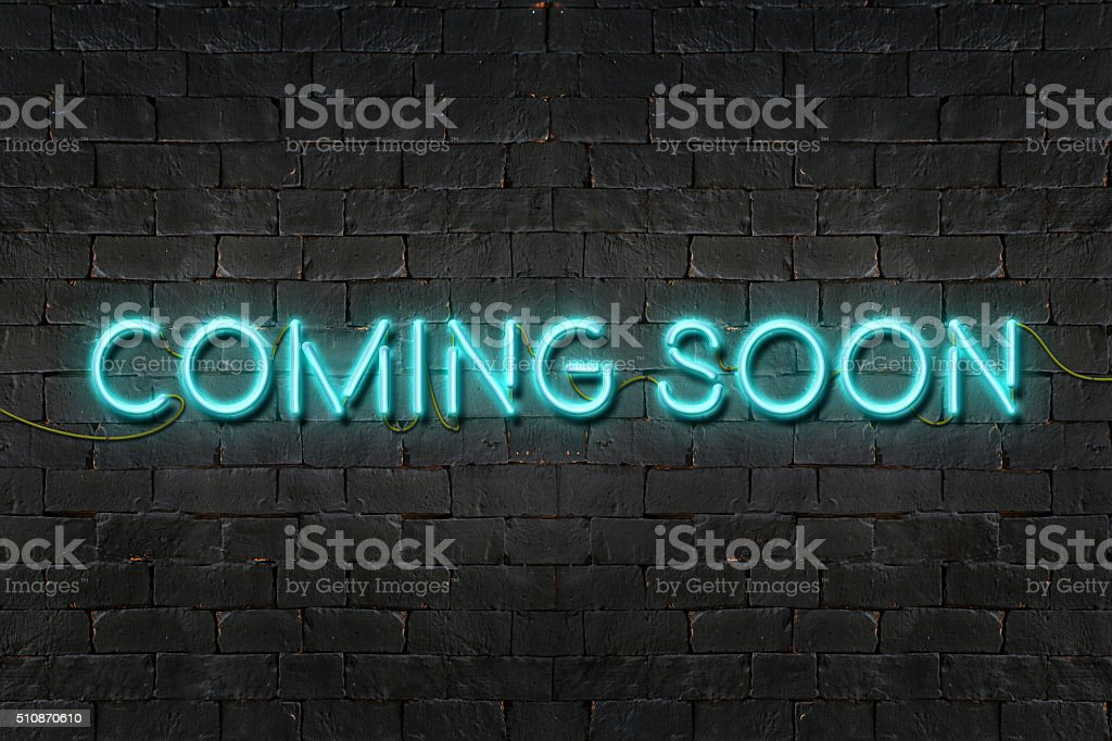 'COMING SOON' neon sign shining on black brick wall stock photo