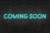 'COMING SOON' neon sign shining on black brick wall