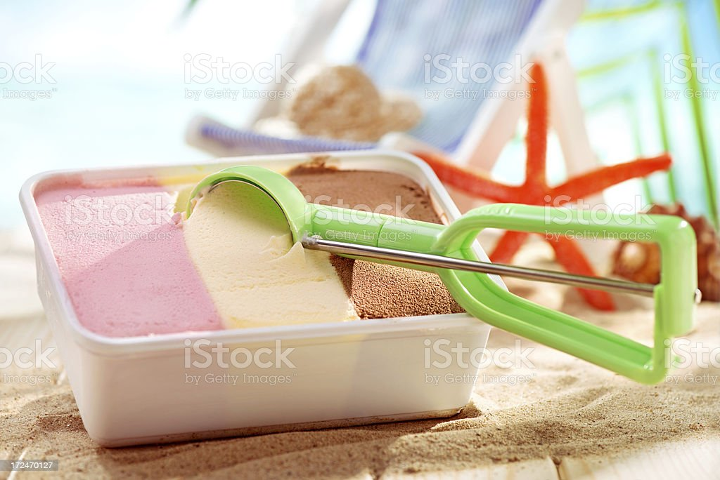 Neopolitan ice cream close up with scoop on beach background royalty-free stock photo