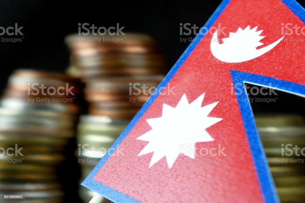 Nepal flag waving with stack of money coins macro stock photo