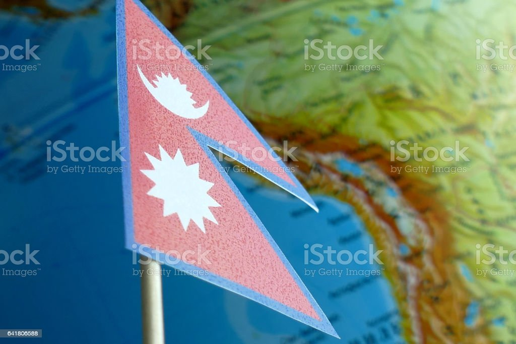 Nepal flag with a globe map as a background macro stock photo