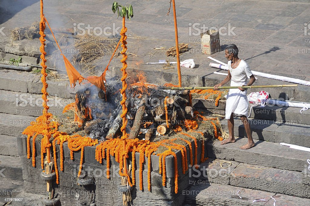 Nepal Scene: Man makes cremation in Pashupatinath Temple in Kathmandu stock photo
