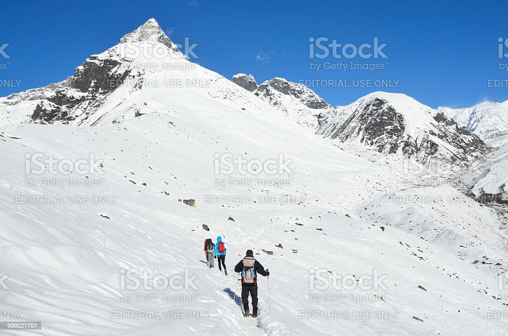 Nepal Scene: trekking in the Himalayas, tourists on the trail stock photo