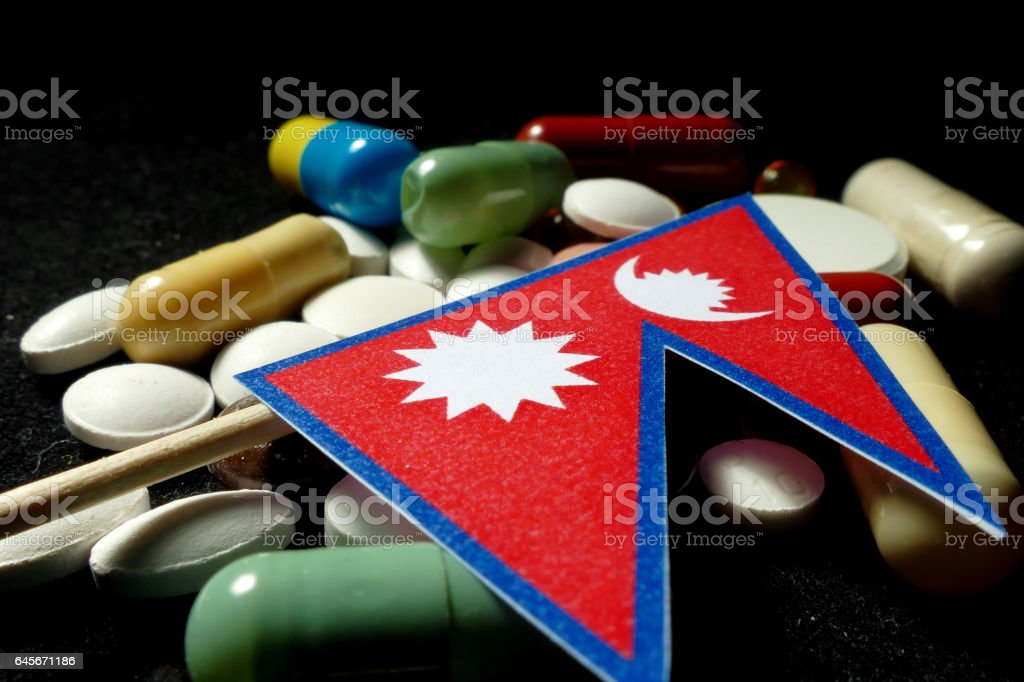 Nepalese flag with lot of medical pills isolated stock photo