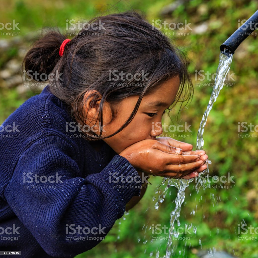 Nepalese girl drinking water, village near Annapurna Range stock photo