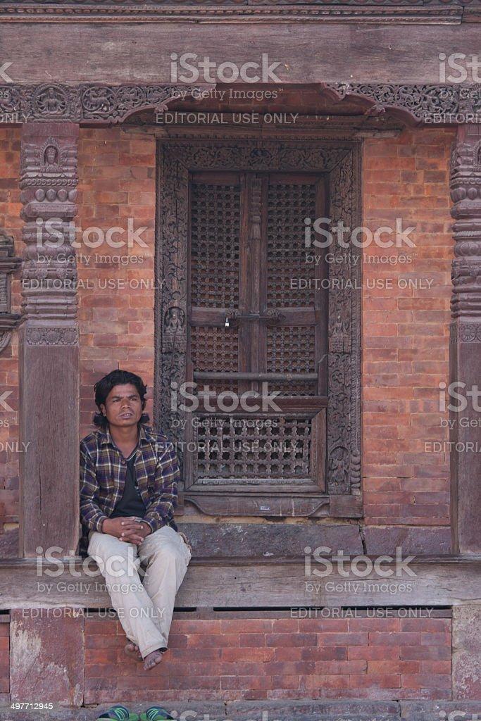 Nepalese man sitting at  ancient temple in Kathmandu? Nepal stock photo